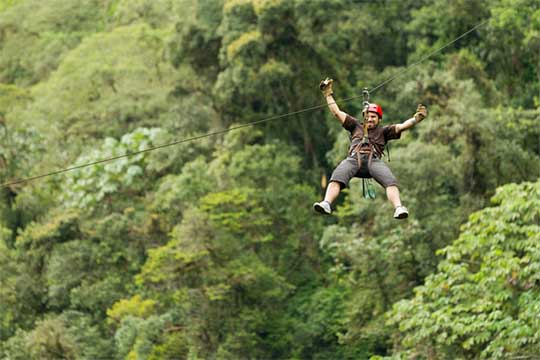 A man rides a zipline over the hills of the Ozark Mountains